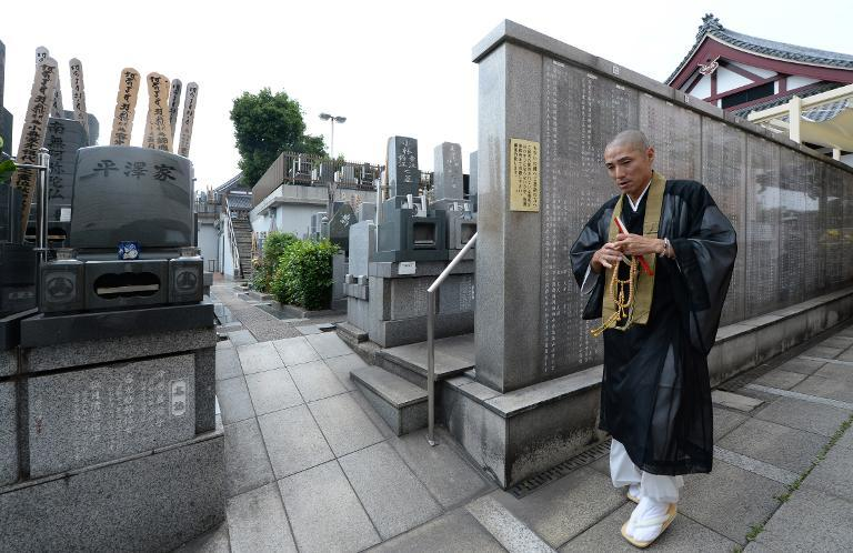 Ryukai Matsushima, a Buddhist priest whose father pioneered a movement of seeking gravemates, walks past a communal resting place at his temple in Tokyo, June 4, 2014