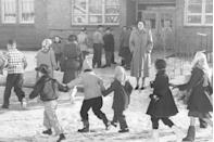 <p>A teacher welcomes her students back to class following the holiday break.</p>