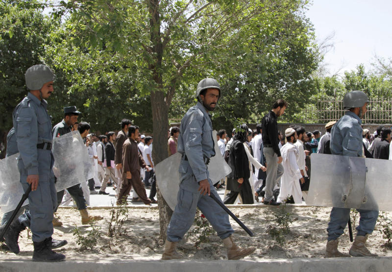 Afghan riot policemen move into position during a demonstration in Kabul, Afghanistan, Wednesday, May, 22, 2013. More than 200 male students protested in front of Kabul University on Wednesday against a decree, which includes a ban on child marriage and forced marriage, making domestic violence a crime and saying that rape victims cannot be prosecuted for adultery.(AP Photo/Ahmad Jamshid)