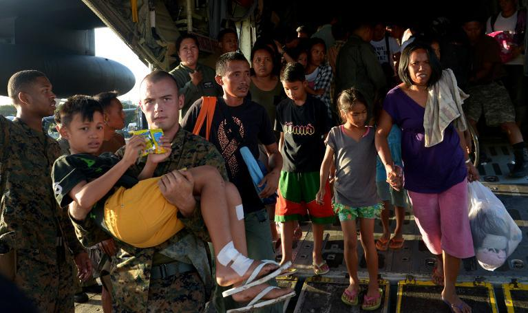 A US marine (L) carries an injured boy who survived the wrath of Super Typhoon Haiyan in the central coastal city of Tacloban, as they disembark from a military cargo plane that flew them out of the city to Manila on November 12, 2013