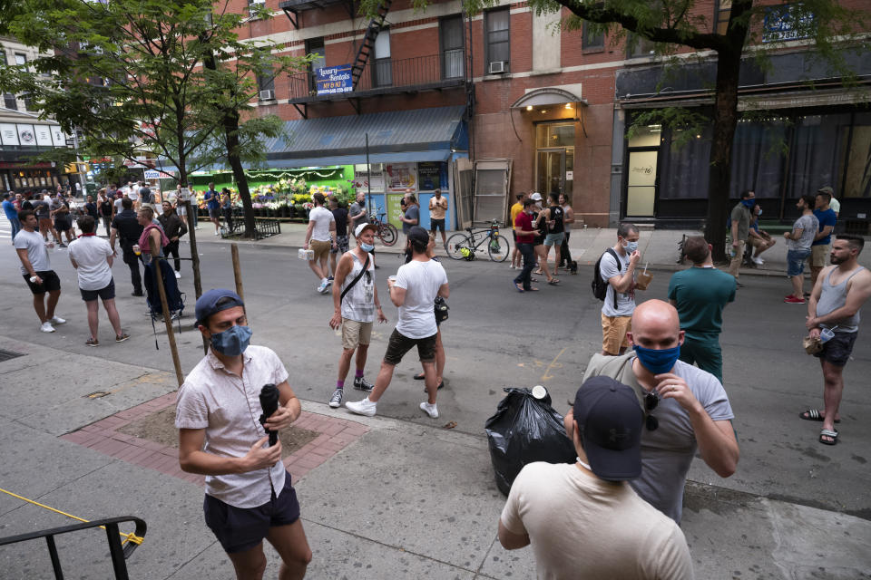 People gather on a street in the Hell's Kitchen neighborhood of New York, Friday, May 29, 2020, during the coronavirus pandemic. The street has been blocked off from traffic to allow residents to gather in open spaces with some social distancing. (AP Photo/Mark Lennihan)