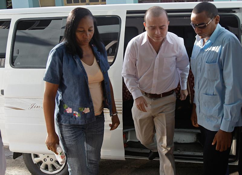 **CORRECTS BYLINE** Cuban security forces escort Spanish citizen Angel Carromero, center, to the courthouse to attend his trial in Bayamo, Cuba, Friday Oct. 5, 2012. Carromero went on trial Friday in connection with a car crash in which a prominent dissident Oswaldo Paya and another dissident, Harold Cepero, were killed. (AP Photo/Ismael Francisco, Pool)