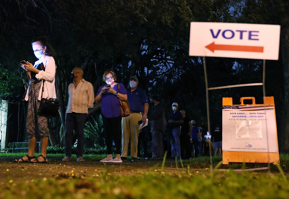 CORAL GABLES, FLORIDA - OCTOBER 19: Voters wait in line to cast their early ballots at the Coral Gables Branch Library precinct on October 19, 2020 in Coral Gables, Florida. The early voting ends on Nov. 1. Voters are casting their ballots for presidential candidates President Donald Trump and Democratic presidential nominee Joe Biden. (Photo by Joe Raedle/Getty Images)