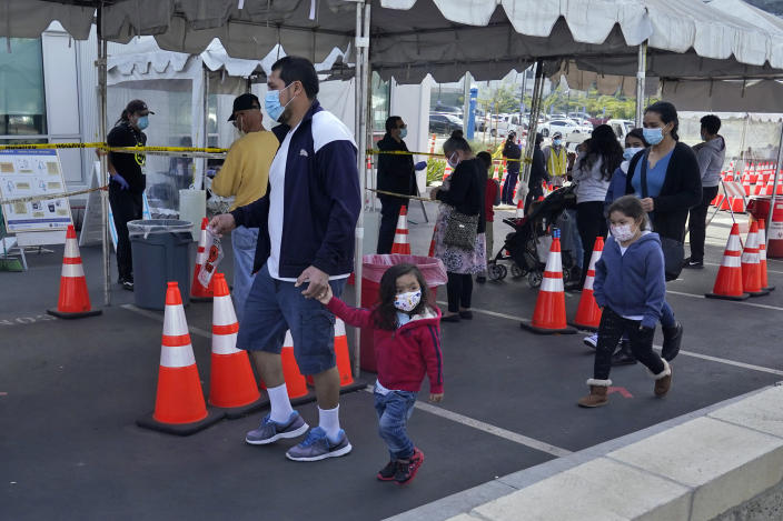 FILE - In this Jan. 7, 2021, file photo, people walk to a tent at a COVID-19 walk-up testing site on the Martin Luther King Jr. Medical Campus in Los Angeles, Jan. 7, 2021. Coronavirus deaths and cases per day in the U.S. dropped markedly over the past couple of weeks but are still running at alarmingly high levels, and the effort to snuff out COVID-19 is becoming an ever more urgent race between the vaccine and the mutating virus. (AP Photo/Marcio Jose Sanchez, File)