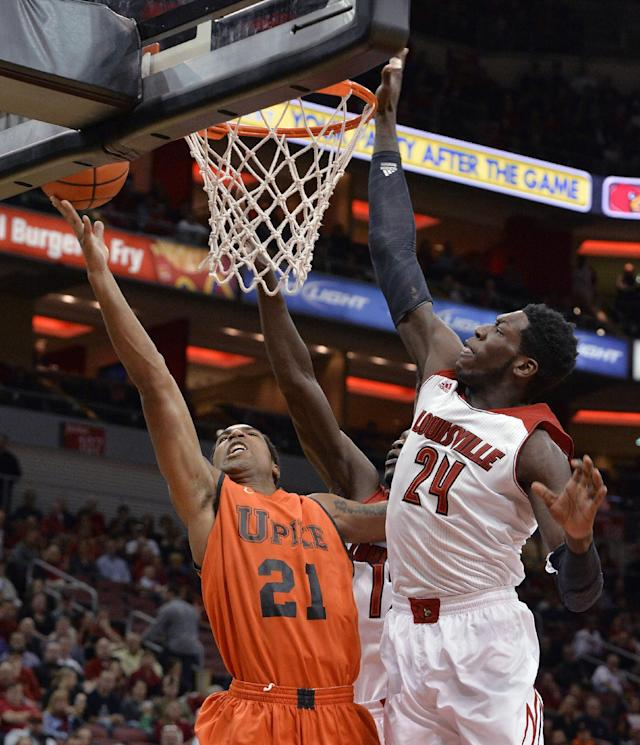 Pikeville's Bruce Reed, left, attempts a shot over the defense of Louisville's Montrezl Harrell during the first half of an NCAA college basketball exhibition game, Wednesday, Nov. 6, 2013, in Louisville, Ky. (AP Photo/Timothy D. Easley)