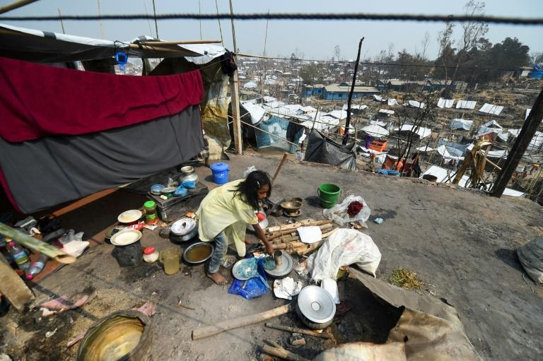 A Rohingya refugee child arranges utensils in a temporary shelter