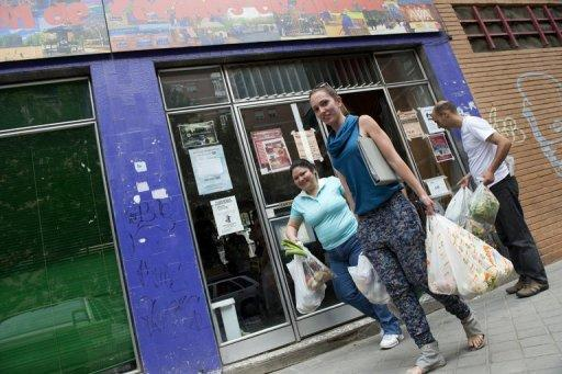 "People carry bags filled up with fruits and vegetables for distribution to the needy, in a working class neighbourhood of Madrid, on June 1. Spain's ""indignants"" are currently building an extraordinary street-level network to help those hardest hit by economic hardship"