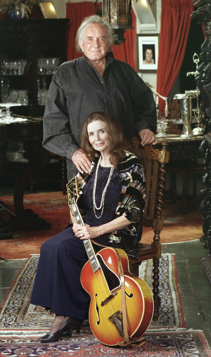 "FILE - In this 1999, file photo, the late country music legend Johnny Cash poses with his wife, the late June Carter Cash, in their Hendersonville, Tenn., home. The Man in Black is about to get his own day in Arkansas. The Arkansas House on Tuesday, April 20, 2021, gave unanimous final approval to a bill that would make Feb. 26 ""Johnny Cash Day,"" sending it to Gov. Asa Hutchinson, who plans to sign it. (AP Photo/Mark Humphrey/File)"