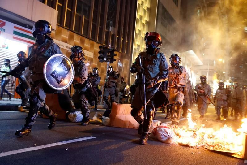 """FILE PHOTO: Police pass a burning barricade to break up thousands of anti-government protesters during a march billed as a global """"emergency call"""" for autonomy, in Hong Kong"""