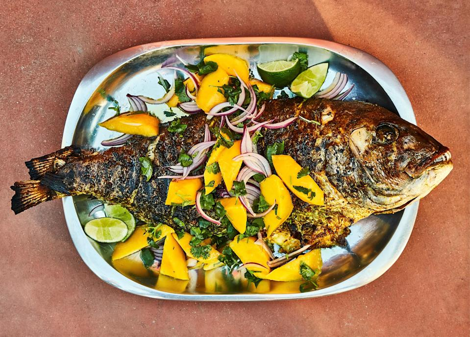 "Grilling a whole fish doesn't have to be daunting, especially if you use this turning method to minimize the risk of tearing the skin. Lay the fish horizontally across the grill grate with the top fins toward you and cook. When it's time to turn, wedge two metal spatulas under the fish—one near the tail and the other at the head—then quickly and confidently roll it away from you onto its other side in one fluid motion. <a href=""https://www.bonappetit.com/recipe/spiced-snapper-with-mango-and-red-onion-salad?mbid=synd_yahoo_rss"" rel=""nofollow noopener"" target=""_blank"" data-ylk=""slk:See recipe."" class=""link rapid-noclick-resp"">See recipe.</a>"