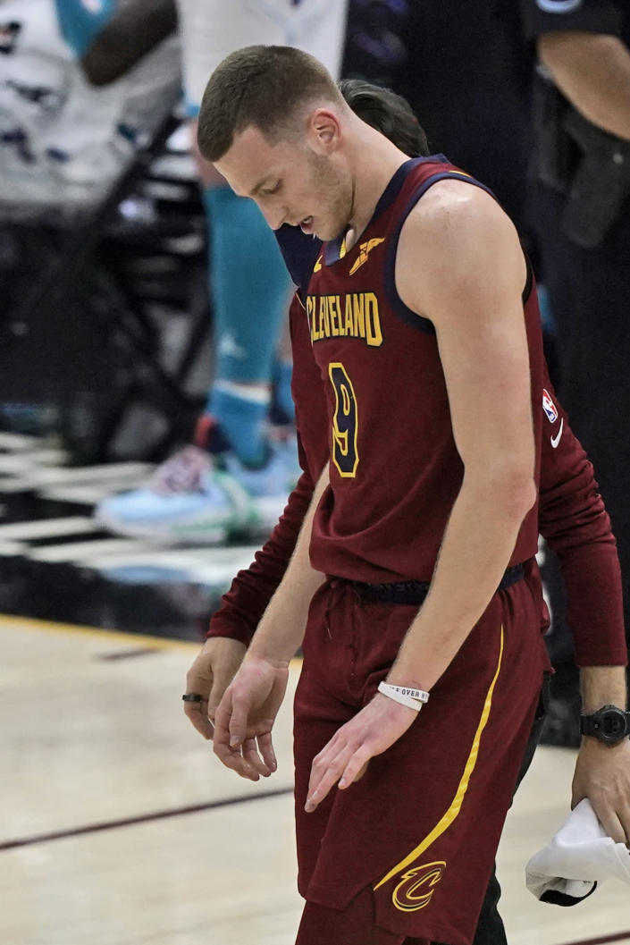 Cleveland Cavaliers' Dylan Windler looks down at his hand as he walks off the court after breaking his left hand in the season opener in the second half of an NBA basketball game against the Charlotte Hornets, Wednesday, Dec. 23, 2020, in Cleveland. The team said Thursday that Windler suffered a fourth metacarpal fracture when he took a hard fall in the third quarter against Charlotte. X-rays after the game were negative, but further tests revealed the fracture. (AP Photo/Tony Dejak)