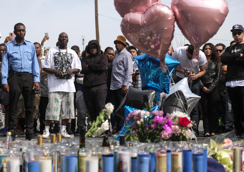 Fans of rapper Nipsey Hussle appear at a makeshift memorial in the parking lot of Hussle's Marathon Clothing store in Los Angeles, Monday, April 1, 2019. Hussle was killed in a shooting outside the clothing store on Sunday. (AP Photo/Ringo H.W. Chiu)