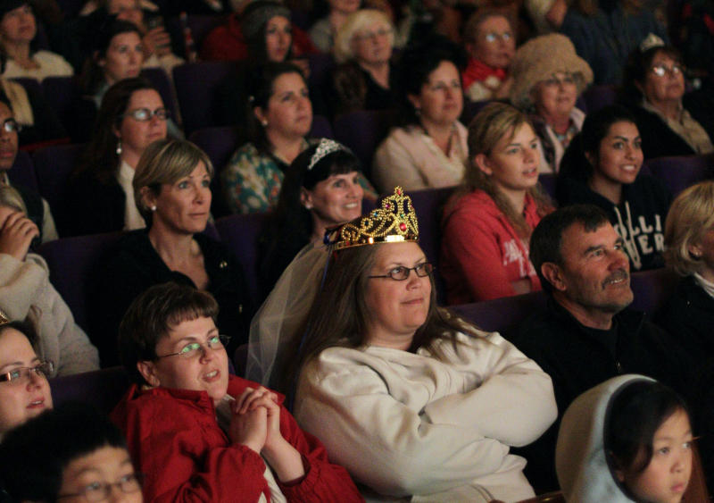 "FILE - In this April 29, 2011, file photo, Sandy Weimer, wearing tiara, and Cathy Dettman, left, attend a royal wedding ""hat and pajamas"" party at the Cameo Cinema in St. Helena, Calif., where more than150 people filled the theater in the middle of the night to watch a live broadcast of the royal wedding of Britain's Prince William and Kate Middleton. The palace announced Monday, Dec. 3, 2012, that Prince William and wife Kate are expecting their first child_and it seems at times that Americans may be more enthralled than the Brits. There are several reasons for the American public's pleasure in Kate's news, manifested not only by the good wishes sent by President Obama but also by the breathless news coverage and the general good will toward the couple. (AP Photo/Eric Risberg, File)"