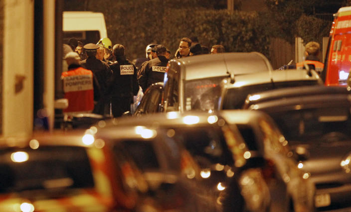 French police officers and firefighters stand at night next to the apartment building where a suspect in the shooting at the Ozar Hatorah Jewish school is still barricaded, in Toulouse, Southern France, Wednesday, March 21, 2012. A predawn police raid on a home in Toulouse erupted into a firefight Wednesday with a gunman who claims connections to al-Qaida and is suspected of killing three Jewish schoolchildren, a rabbi and three paratroopers. (AP Photo/Christophe Ena)