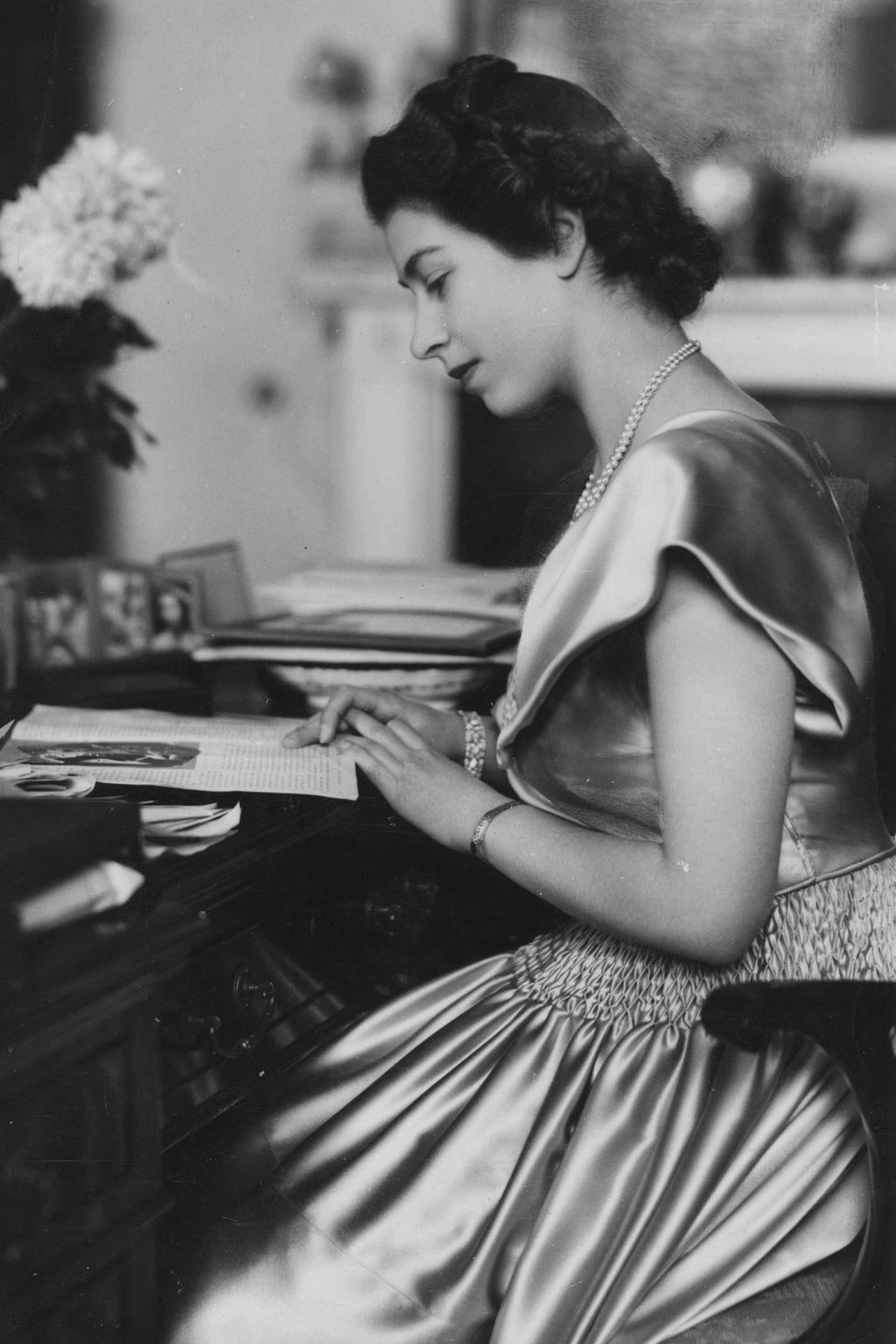 <p>The queen wore a satin dress, pearl necklace, and bracelets while she read at her desk in Buckingham Palace.</p>