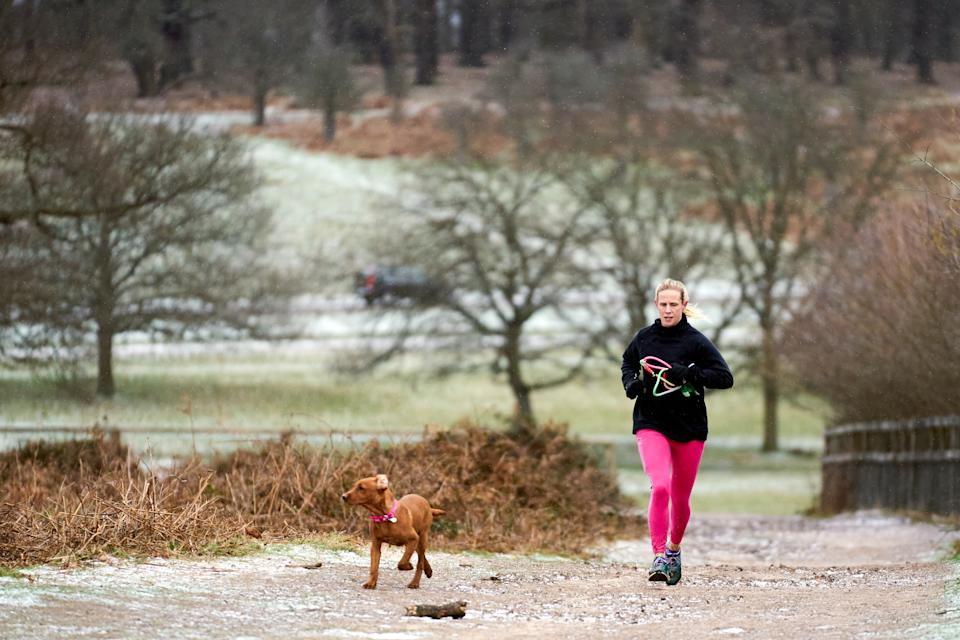 A runner exercising with her dog in Richmond Park, London, the Met Office has issued a severe amber snow warnings for London and south-east England, where heavy snow is likely to cause long delays on roads and with rail and air travel. Picture date: Monday February 8, 2021.