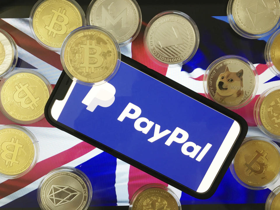 A stylised image of a phone, displaying the PayPal image, with various cryptocurrencies and the Union Jack flag. Source: AP