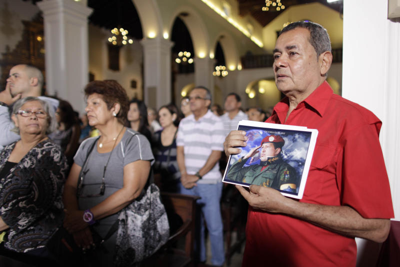 """People, one of them holding an image of Venezuela's President Hugo Chavez, gather to pray for him at a church in Caracas, Venezuela, Monday, Dec. 31, 2012. Venezuela's President Hugo Chavez is confronting """"new complications"""" due to a respiratory infection nearly three weeks after undergoing cancer surgery, his Vice President Nicolas Maduro said Sunday evening in Cuba as he visited the ailing leader for the first time since his operation. (AP Photo/Ariana Cubillos)"""