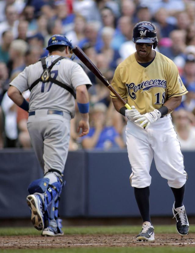 Milwaukee Brewers' Khris Davis, left, reacts after striking out against the Los Angeles Dodgers during the fourth inning of a baseball game Sunday, Aug. 10, 2014, in Milwaukee. (AP Photo/Darren Hauck)