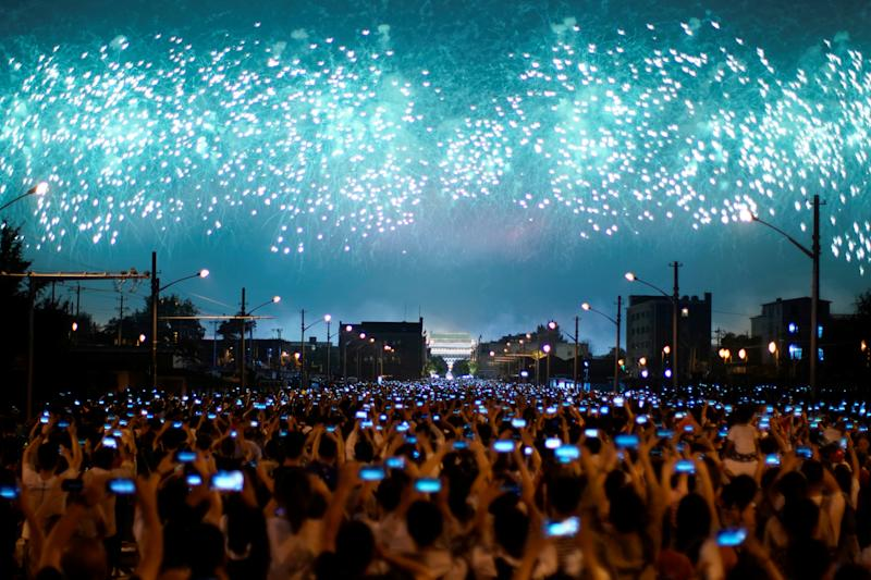 People on the street hold their phones as fireworks explode in the sky during an evening gala marking the 70th anniversary of the founding of the People's Republic of China, on its National Day in Beijing, China October 1, 2019. (Photo: Aly Song/Reuters)