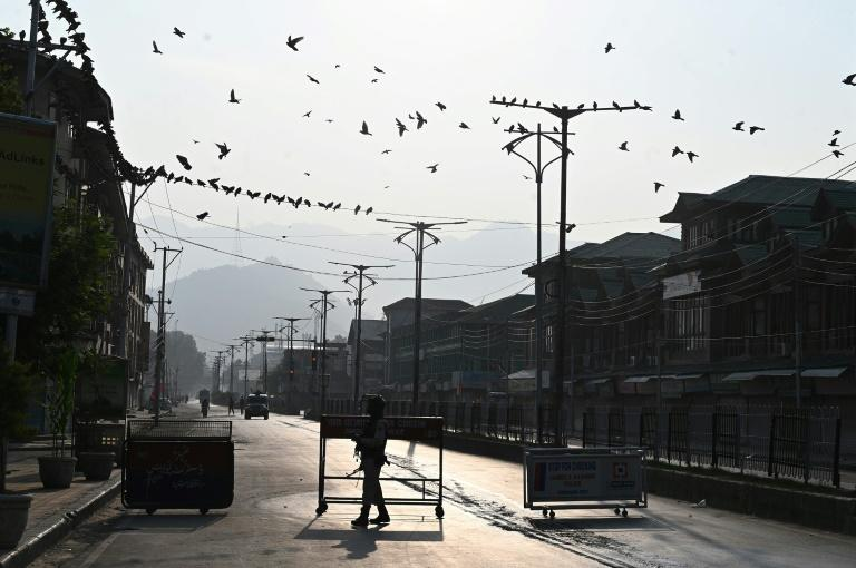 A security officer stands guard at a roadblock in Srinagar, the main city of Indian-administered Kashmir which remained virtually cut off from the outside world and under a security lockdown (AFP Photo/Tauseef MUSTAFA)