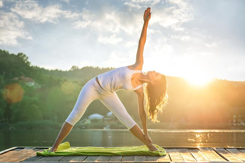 A woman holds a yoga pose on a dock next to a lake with the sun shining in the background