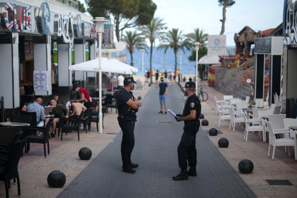 """Police officers patrol at the resort of Magaluf on the Spanish Balearic island of Mallorca, Spain, Thursday, July 16, 2020. In a move designed to stop the spread of the new coronavirus and shake off the region's reputation as a party hub, regional authorities in the Balearic Islands ordered the closure from Thursday of all establishments along Mallorca's """"Beer St."""" and """"Ham St."""", as the popular party areas near the beach of Palma de Mallorca are known, and another boulevard in nearby Magaluf. (AP Photo/Joan Mateu)"""