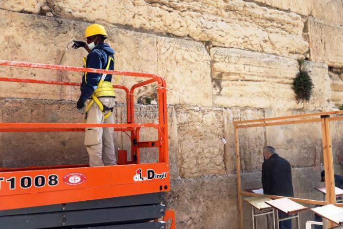 A labourer stands on a portable lift as he injects a type of grout into gaps and fissures in the stones of the Western Wall, Judaism's holiest prayer site, as part of the Israel Antiquities Authority treatment of the ancient stones, in Jerusalem's Old City