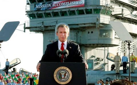In this May 2, 2003 file photo, President George W. Bush declares the end of major combat in Iraq as he speaks aboard the aircraft carrier USS Abraham Lincoln off the California coast - Credit: AP