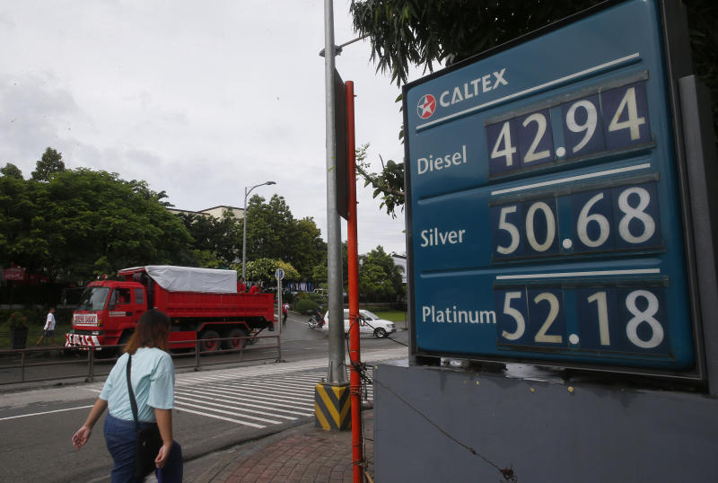A commuter walks past a huge sign of the new pump prices of gasoline and diesel following its implementation Tuesday, Sept. 17, 2019, in suburban Valenzuela city north of Manila, Philippines. Monday saw another round of oil price increase in the country which energy officials said is not related to the recent attacks in Saudi Arabia but has cautioned the public to brace for more spikes in the coming days. (AP Photo/Bullit Marquez)