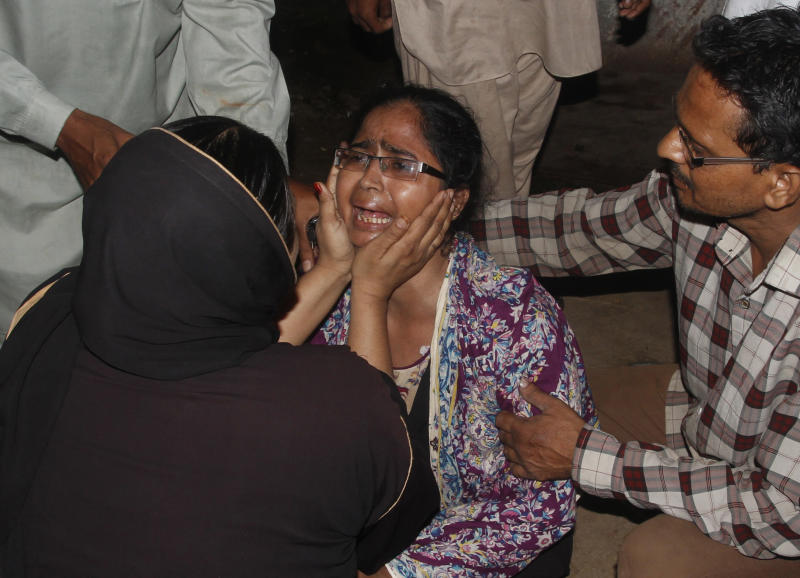 People comfort a woman who lost her mother in a fire Tuesday, Sept. 11, 2012 in Karachi, Pakistan. Factory fires in two of Pakistan's major cities killed 39 people and injured dozens more on Tuesday, including some who had to break through barred windows and leap to the ground to escape the flames. (AP Photo/Shakil Adil)