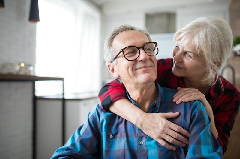 Older woman putting her arms around older man