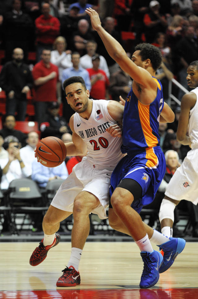 San Diego State's JJ O'Brien (20) tries to drive past San Jose State's Devante Wilson (22) during the first half of an NCAA college basketball game on Tuesday, Feb. 25, 2014, in San Diego. (AP Photo/Denis Poroy)
