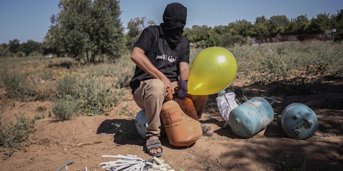 A masked Palestinian supporter of the Al-Nasir Salah Al-Din Brigades prepares incendiary balloons to launch across the border fence east of Gaza city towards Israel, on June 16, 2021 east of Gaza City in Gaza. The flare-up came after a controversial flag-waving march by Israeli nationalists was allowed to proceed through East Jerusalem on Tuesday, stoking tensions in Israel and Gaza less than a month after a ceasefire ended 11 days of fighting between Hamas and Israeli forces.