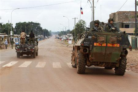 A French military vehicle patrols past Seleka soldiers during fighting between Muslim and Christian militias in Bangui