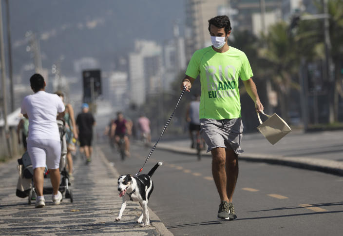 A man jogs with his dog in the bike lane that runs along the seashore at Ipanema beach in Rio de Janeiro, Brazil, Tuesday, June 2, 2020, amid the new coronavirus pandemic. Rio, the city with the second-most cases after Sao Paulo, is beginning to gradually relax restrictions on Tuesday, allowing people to exercise on the beachfront sidewalk and practice individual activities in the sea. (AP Photo/Silvia Izquierdo)