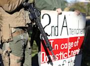 """A man carries a rifle as militia members and pro-gun rights activists participating in the """"Declaration of Restoration"""" rally prepare to march to Washington, D.C. from Arlington, Virginia"""