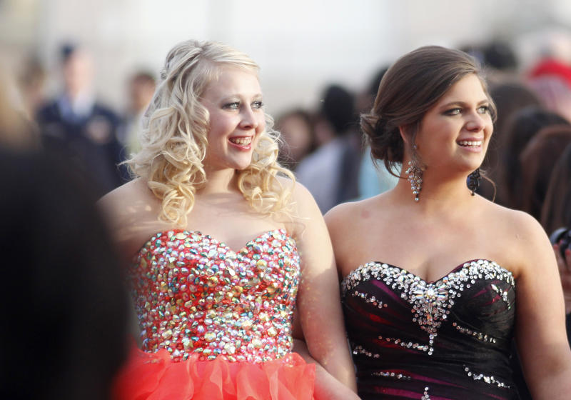 In this April 20, 2013 photo, Courtney Widener, right, walks up the red carpet with a friend as her brother, U.S. Airman Casey Widener, left background, out of focus, watches their arrival at Liberal High School in Liberal, Kan. Courtney wanted her brother, Senior Airman Casey Widener, recently returned from Afghanistan, to escort her to front door of the school, but school officials denied her request stating that at 22, he was too old to participate. The high school principal responsible for the denial has apologized, saying the intent was not to dishonor him. Deputy Superintendent Paul Larkin said Tuesday, April 30, 2013 that a policy change allowing exceptions to the age restriction will be presented at Monday's school board meeting. (AP Photo/Leader & Times, Earl Watt)