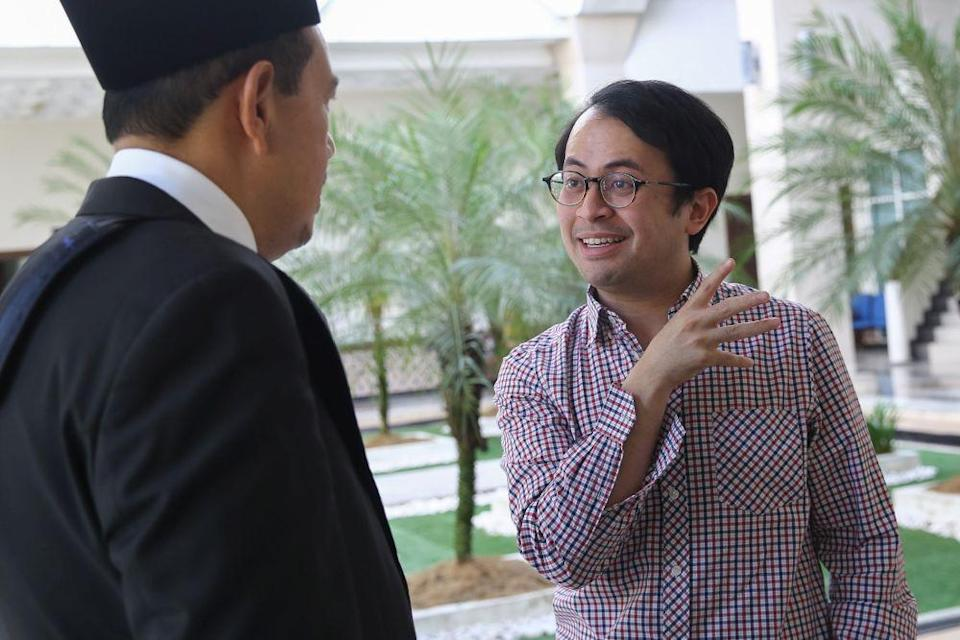 Mohd Ezra Mohd Zaid speaks with his lawyer Zulkifli Che Yong at the Petaling Jaya District Syariah Subordination Court October 17, 2019. — Picture by Yusof Mat Isa
