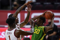 Oregon forward Eric Williams Jr. (50) keeps the ball away from Southern California forward Chevez Goodwin (1) and guard Isaiah White, center, during the first half of an NCAA college basketball game Monday, Feb. 22, 2021, in Los Angeles. (AP Photo/Ashley Landis)