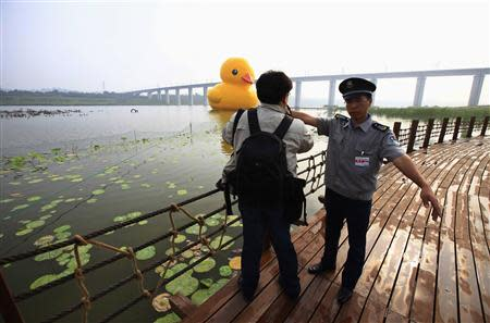 A security guard tries to ask a photographer to leave as he takes pictures of an inflated Rubber Duck by Dutch conceptual artist Florentijn Hofman floating on a lake at the 9th China International Garden Expo in Beijing, September 6, 2013. REUTERS/Petar Kujundzic