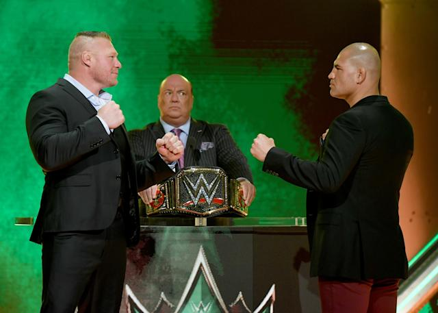 Brock Lesnar (L) and Cain Velasquez (R) face off as Lesnar's advocate Paul Heyman (C) looks on during the announcement of their match at a WWE news conference at T-Mobile Arena on Oct. 11, 2019 in Las Vegas. (Ethan Miller/Getty Images)