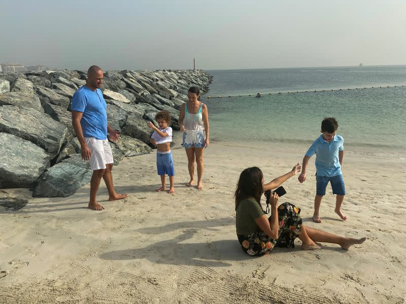 Paula Hainey, a photographer gives a free family photo session at a beach to Muhammad Shehata and his family as they will be leaving Dubai, in Dubai