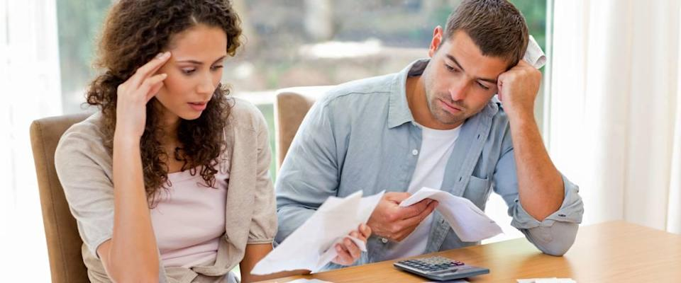 Young couple calculating their domestic bills at home.