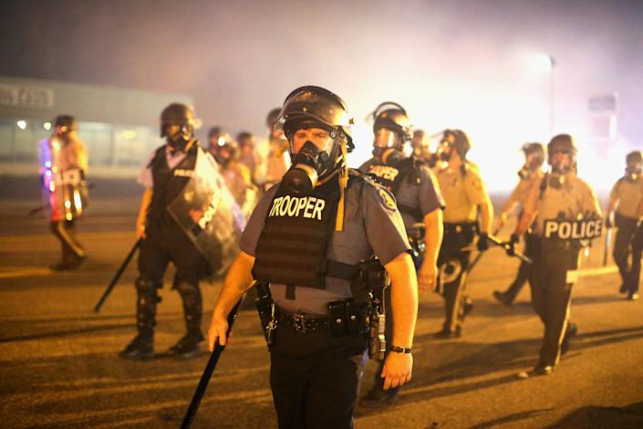 Police advance through a cloud of tear gas toward demonstrators protesting the killing of teenager Michael Brown on August 17, 2014 in Ferguson, Missouri. (Photo by Scott Olson/Getty Images)
