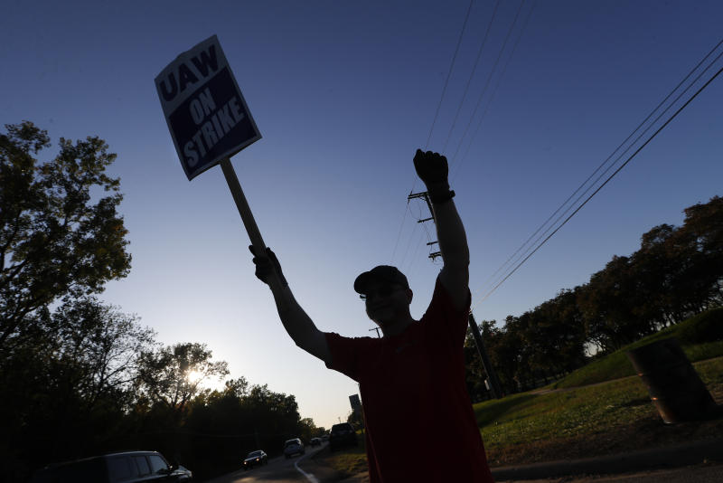 A member of the United Auto Workers cheers on honking cars as he walks the picket line at the General Motors Romulus Powertrain plant in Romulus, Mich., Wednesday, Oct. 9, 2019. Nearly four weeks into the United Auto Workers' strike against GM, employees are starting to feel the pinch of going without their regular paychecks. (AP Photo/Paul Sancya)