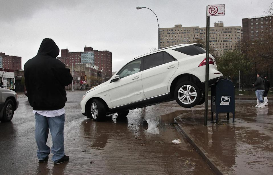 The tailend of a SUV is perched on top of a postal mailbox in the aftermath of floods from Hurricane Sandy on Tuesday, Oct. 30, 2012, in Coney Island, N.Y. Sandy, the storm that made landfall Monday, caused multiple fatalities, halted mass transit and cut power to more than 6 million homes and businesses. (AP Photo/Bebeto Matthews)