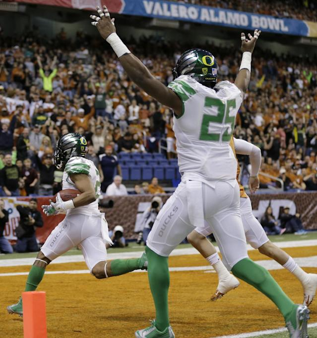 Oregon's Avery Patterson, left, scores with an interception against Texas during the first quarter in the Valero Alamo Bowl NCAA college football game, Monday, Dec. 30, 2013, in San Antonio. (AP Photo/Eric Gay)