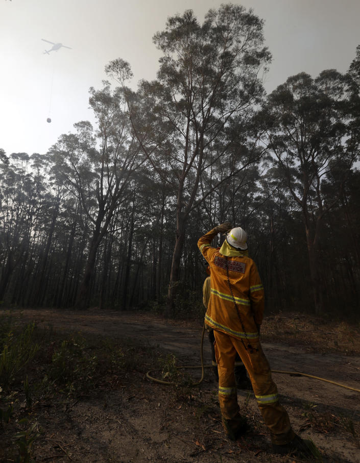 A firefighter watches a water bombing helicopter approach as they battle a fire near Bendalong, Australia, Friday, Jan. 3, 2020. Navy ships plucked hundreds of people from beaches and tens of thousands were urged to flee before hot, windy weather worsens Australia's devastating wildfires. (AP Photo/Rick Rycroft)