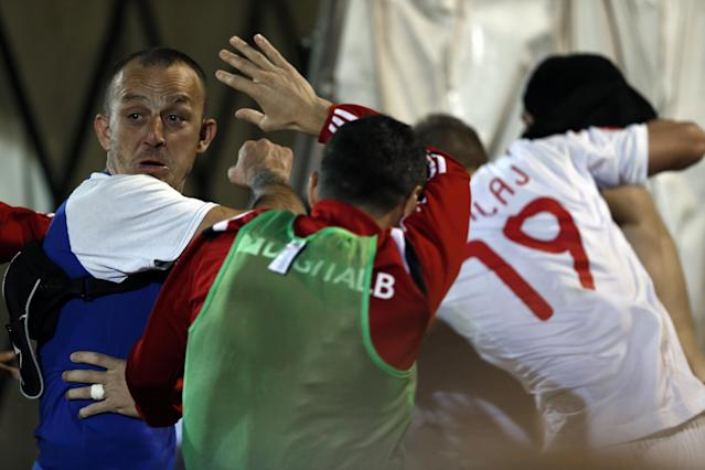 A Serbian national team supporter, left, attacks members of the Albanian national soccer team during the Euro 2016 Group I qualifying match between Serbia and Albania at the Partizan stadium in Belgrade, Serbia, Tuesday, Oct. 14, 2014. The European Championship qualifier between Serbia and Albania was suspended on Tuesday after pitch skirmishes involving players and fans over an Albanian flag banner that was flown above the stadium by a drone. (AP Photo/Marko Drobnjakovic)